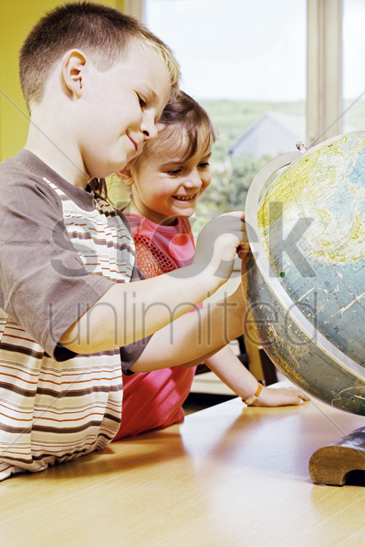 boy and girl referring to a globe stock photo