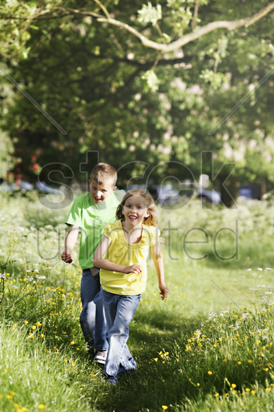 boy and girl running in the park stock photo