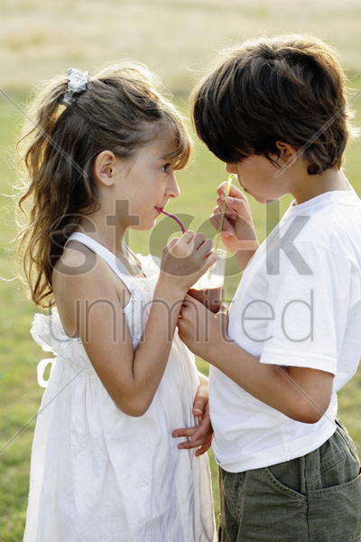boy and girl sharing a cup of hot drink stock photo