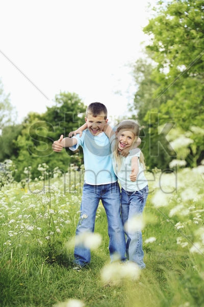boy and girl showing thumbs up stock photo