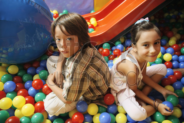 boy and girl sitting in ball pool stock photo