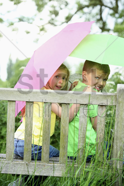 boy and girl sitting on a bench hodlign umbrellas stock photo