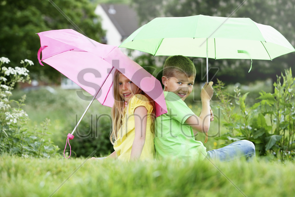 boy and girl sitting on field holding umbrellas stock photo