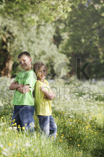 boy and girl standing with their backs facing each other stock photo