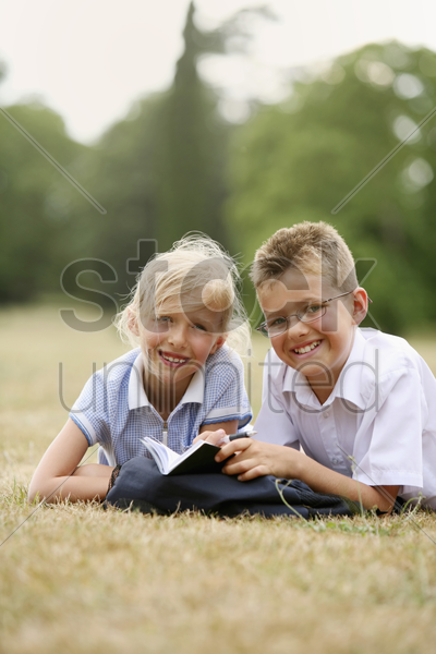 boy and girl studying together in the park stock photo