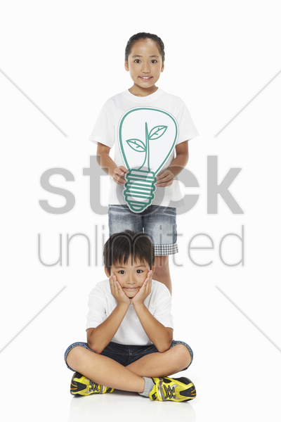 boy and girl with cut out light bulb smiling at the camera stock photo