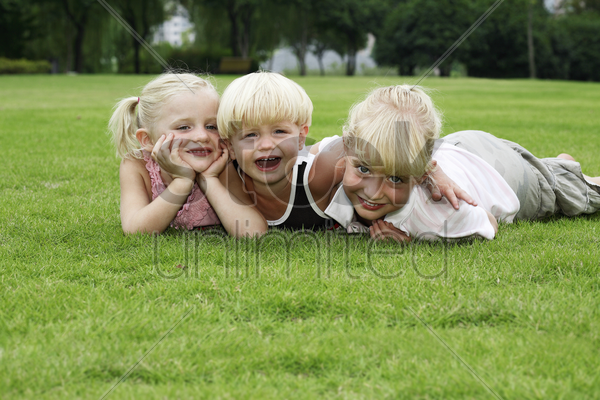 boy and girls lying forward on the field stock photo