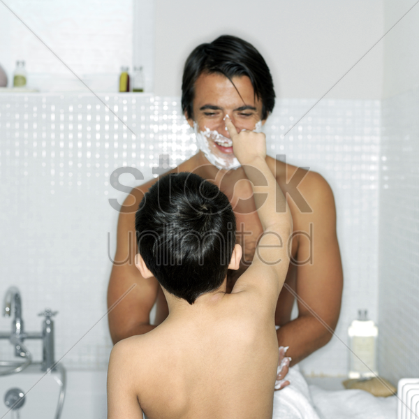 boy applying shaving foam on his father's nose stock photo
