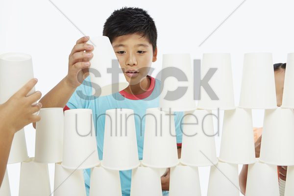 boy arranging a stack of disposable cups stock photo