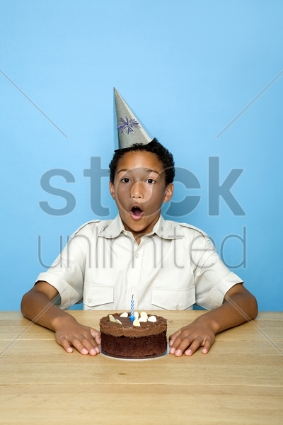boy blowing the candles on the birthday cake stock photo