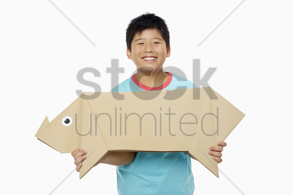 boy carrying a paper pig stock photo