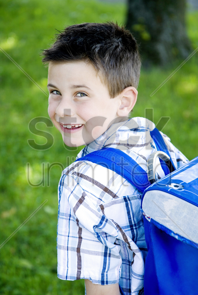 boy carrying school bag on his back stock photo