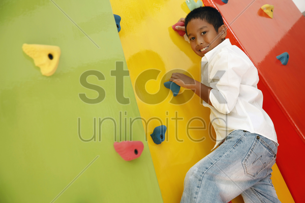 boy climbing rock wall stock photo
