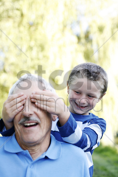 boy covering his grandfather's eyes stock photo