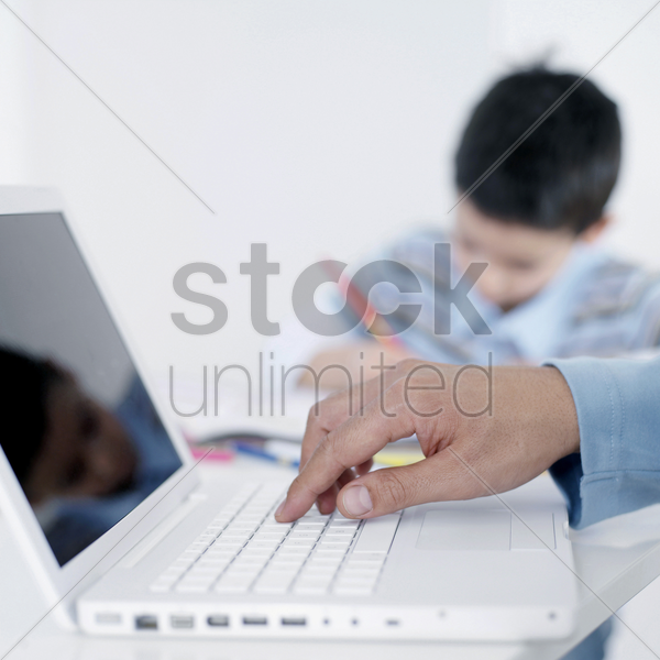 boy doing homework while his father using laptop stock photo
