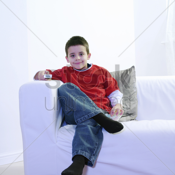 boy eating candy while watching television stock photo