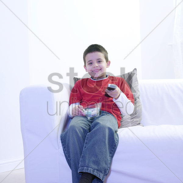 boy holding a bowl of candies while watching television stock photo
