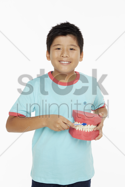 boy holding a set of dentures and brushing it stock photo