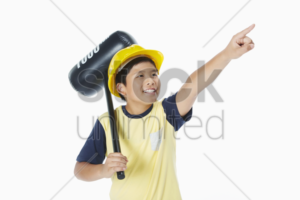 boy holding a toy hammer and pointing to the left stock photo