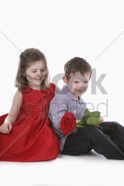 boy holding flower, girl smiling stock photo