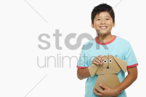 boy holding on to a paper dog stock photo
