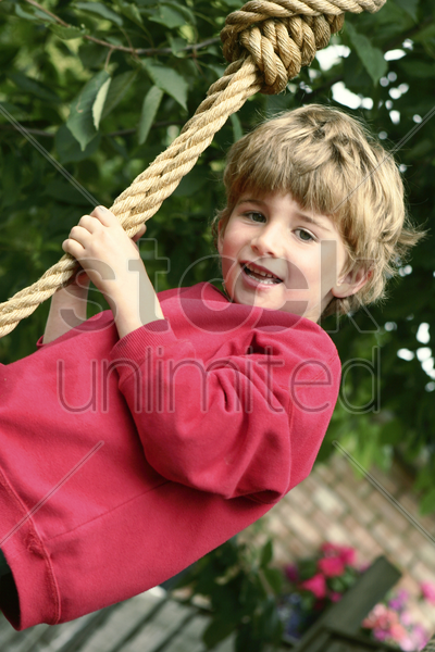 boy holding on to a rope stock photo