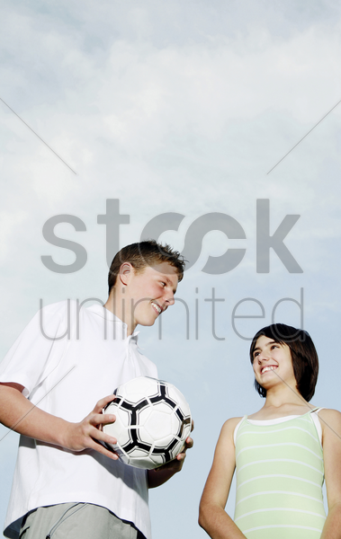 boy holding soccer ball while smiling at his sister stock photo