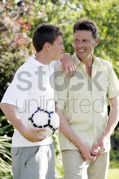 boy holding soccer ball while talking to his father stock photo