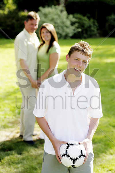 boy holding soccer ball with his parents in the background stock photo