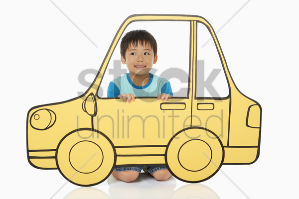 boy holding up a cardboard car stock photo