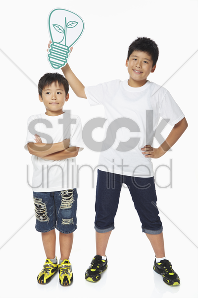 boy holding up a cut out light bulb over another boy's head stock photo