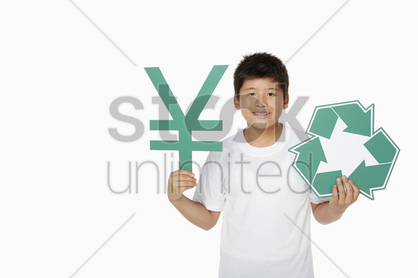 boy holding up a japanese yen symbol and a recycle logo stock photo