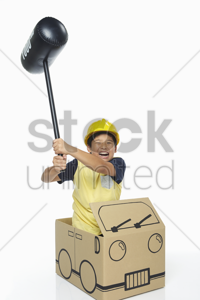boy holding up a toy hammer stock photo