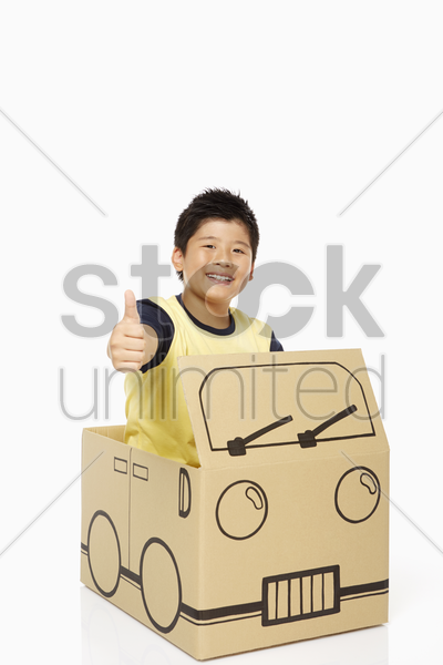 boy in cardboard bus showing hand gesture stock photo