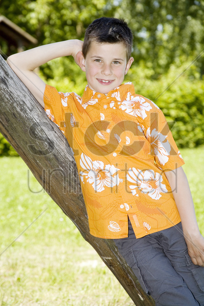 boy leaning against a tree posing for the camera stock photo