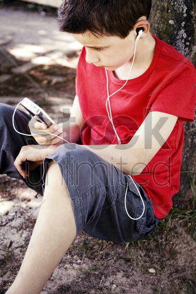 boy listening to music on a portable mp3 player stock photo