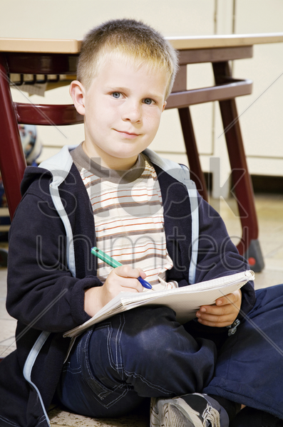 boy looking at the camera while holding a pen and a book stock photo
