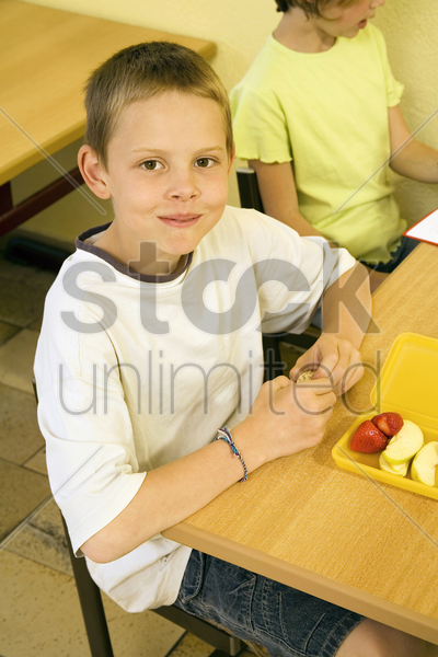 boy looking at the camera with his lunch box on the table stock photo