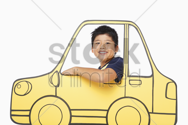 boy looking out a cardboard car window, smiling stock photo