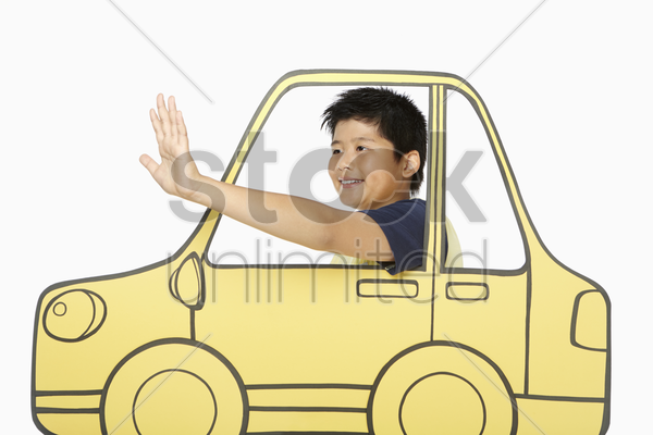 boy looking out a cardboard car window, waving stock photo