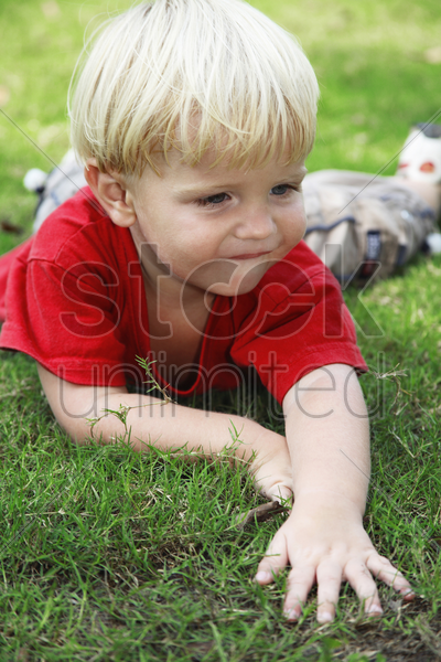 boy lying forward on the field stock photo