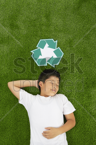 boy lying on the grass stock photo