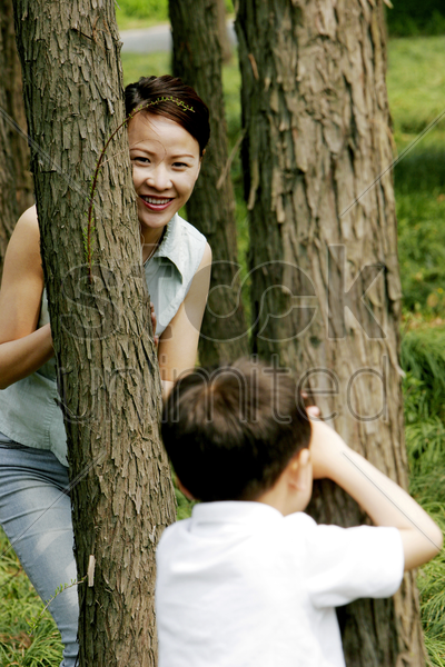 boy playing hide and seek with his mother stock photo
