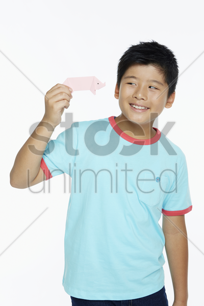 boy playing with a miniature paper pig stock photo
