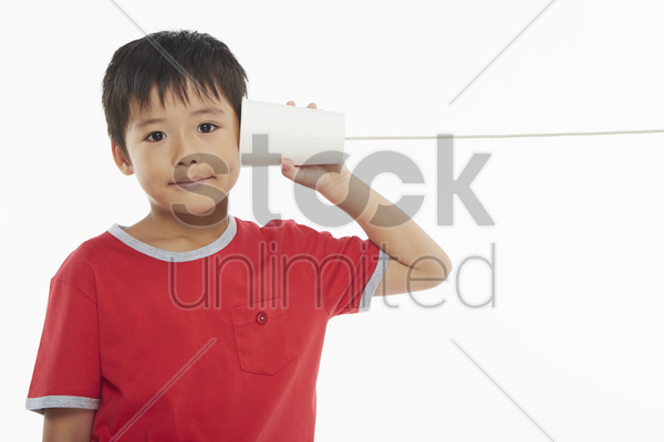 boy playing with a paper cup phone stock photo