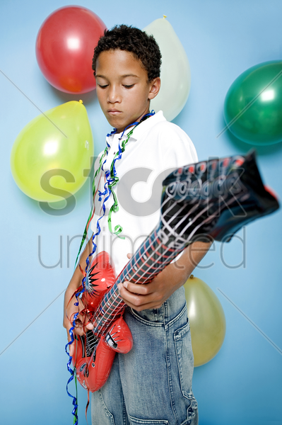 boy playing with an inflatable guitar stock photo