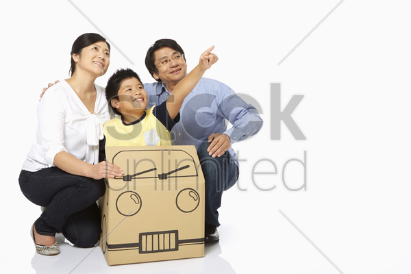 boy pointing to the left as parents look on stock photo