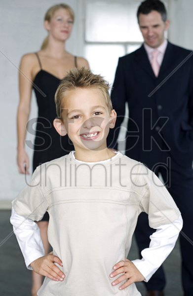 boy posing for the camera with his parents in the background stock photo