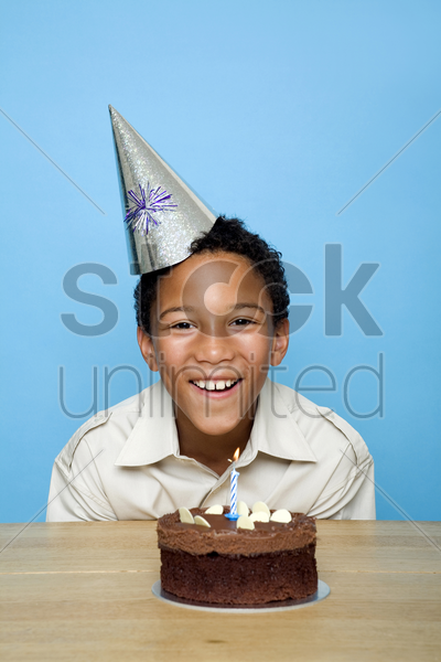 boy posing in front of his birthday cake stock photo