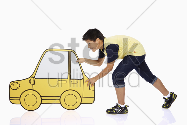 boy pushing a cardboard car stock photo